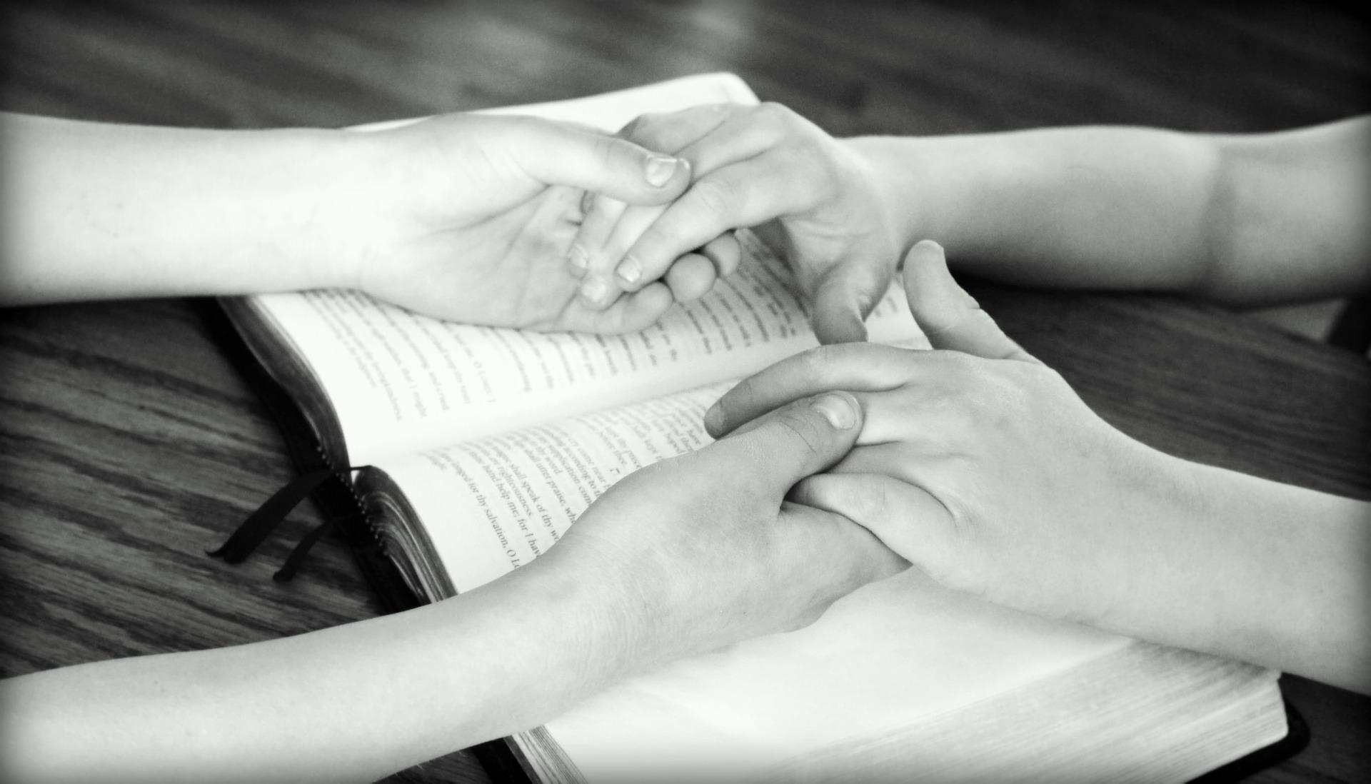 hand die elkaar vasthouden boven een open bijbel