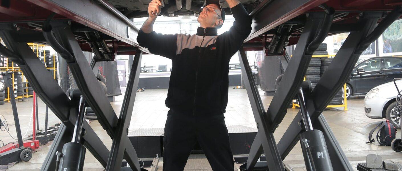 man in black jacket and black pants standing under vehicle